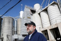 FILE - Matt Aultman, a grain salesman and feed nutritionist with Keller Grain & Feed, Inc., speaks beside grain and soybean silos at their facilities in Greenville, Ohio, April 5, 2018. Rural America is struggling under a cloud of uncertainty as the Trump administration escalates a trade dispute with China.
