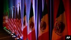 Las banderas de Canadá, Estados Unidos y México son iluminadas durante una conferencia de prensa en el inicio de las negociaciones sobre el TLCAN en Washington el 16 de agosto de 2017.