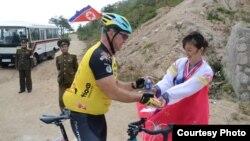 지난 달 말 북한 라선시에서 열린 국제 자전거 경주 대회에 참가한 선수가 북한 주민과 인사를 나누고 있다.. 스웨덴 TT통신 요한 니랜더 (Johan Nylander) 기자 제공.