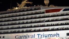 People watch from their balconies and hold up signs aboard the Carnival Triumph after it was towed to the cruise terminal in Mobile, Ala., February 14, 2013.