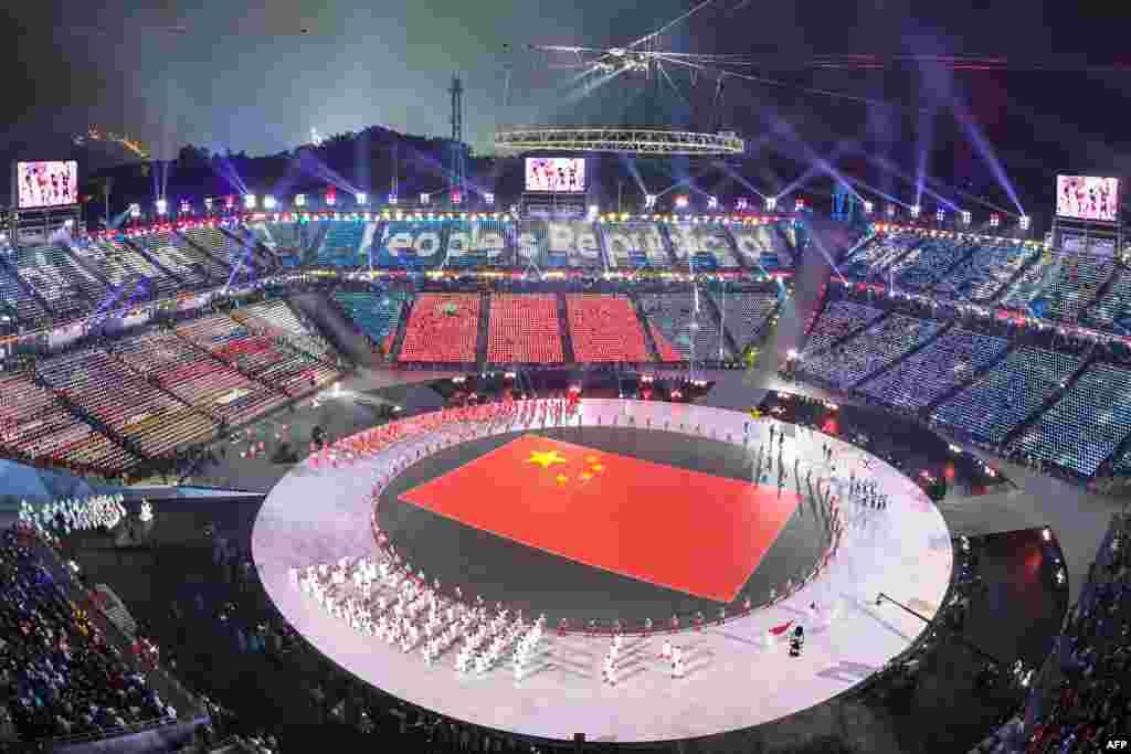 2018年平昌冬奥会开幕式上,中国运动员入场时,平昌体育场显示中国国旗(2018年2月9日)。 开幕式上体育爱好者冒着严寒观看焰火、壮丽灯光秀,以及运动员队伍步入奥运体育场。 本届冬奥会将持续到2月25日结束。