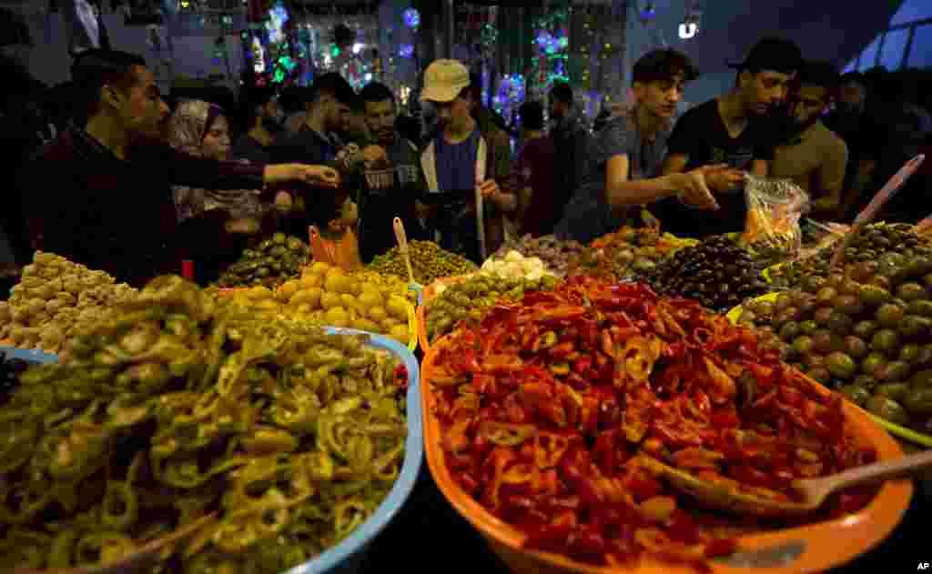 Warga Palestina memperhatikan berbagai penganan acar yang dijual pada Ramadan di sebuah pasar di Kota Gaza, 7 Mei 2019. (Foto: Hatem Moussa/AP)