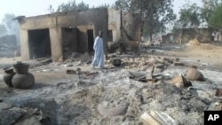 A man walks past burnt out houses following an attack by Boko Haram in Dalori village 5 kilometers (3 miles) from Maiduguri, Nigeria, Jan. 31, 2016.