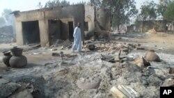 A man walks past burnt out houses following an attack by Boko Haram in Dalori village 5 kilometers (3 miles) from Maiduguri, Nigeria, Jan. 31, 2016.