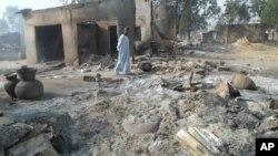 Mtu mmoja anapita kando ya nyumba zilizochomwa kufuatia shambulizi la Boko Haram katika kijiji cha Dalori kilometa 5 kutoka Maiduguri, Nigeria.