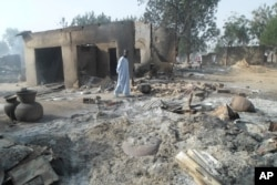 A man walks past burnt-out houses following an attack by Boko Haram in Dalori village 5 kilometers (3 miles) from Maiduguri, Nigeria, Jan. 31, 2016.