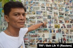 Chairat Ratchapaksi, who founded the Thai and Migrant Fishers Union Group to help trafficked fishermen like him, poses for a photo in front of pictures of rescued trafficking victims in Samut Sakhon, Thailand, March 25, 2018.