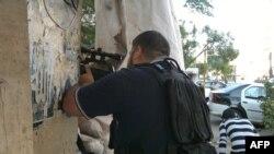 Một dân quân vũ trang núp sau tường chắn tại khu vực Bab al-Tabbaneh của người Hồi giáo Sunni ở thành phố Tripoli, miến bắc Li Băng, ngày 2 tháng 6, 2012