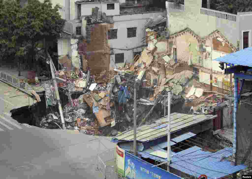 A caved-in area with buildings collapsed inside is seen near the construction site of a new subway line in Guangzhou, Guangdong province, China, January 28, 2013.