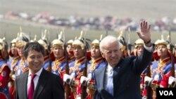 Wapres AS Joe Biden (kanan), didampingi PM Mongolia Batbold Sukhbaatar, melambaikan tangan setibanya di bandara Chinggis Khaan, Mongolia (22/8).
