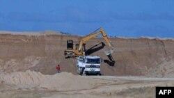 Máy xúc quặng bauxite lên một xe tải tại mỏ của Tập đoàn Khoáng sản Trung Quốc Bosai