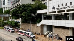 12港人案之一、香港故事成員李宇軒及法律助理陳梓華被控國安法串謀勾結外國勢力罪,8月19日在高等法院答辯,兩人認罪。警方在法院外嚴密佈防 (美國之音/湯惠芸)