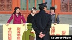 活跃人士在一名警察前面呼吁反家暴立法(北京益仁平中心提供)