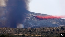 An aerial tanker drops fire retardant on a wildfires threatening homes near Yarnell, Arizona, July 1, 2013.