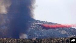 Pesawat militer bertangki air menyiramkan air ke titik-titik api guna mengekang kebakaran di kota Yarnell, Arizona (1/7).