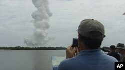 Stephen Bach, a landscape painter from Orlando, Florida, observes the plume left over from the final space shuttle launch in Cape Canaveral, Florida, July 8, 2011