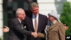 FILE - Israeli Prime Minister Yitzhak Rabin, left, and PLO chairman Yasser Arafat, right, shake hands as President Bill Clinton presides over the ceremony marking the signing of the 1993 peace accord between Israel and the Palestinians on the White House lawn.