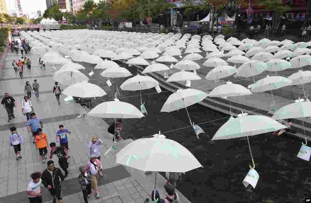 Visitors walk under the umbrellas on display over Cheonggye stream during a campaign to raise money to help poor children in Seoul, South Korea.
