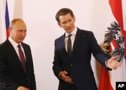 FILE - Austrian Chancellor Sebastian Kurz, right, gestures as he stands with Russian President Vladimir Putin in Vienna, during Putin's visit to Austria, June 5, 2018.