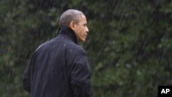 After canceling his appearance at a morning campaign rally in Orlando, Fla., President Barack Obama walks into the White House in a driving rain after returning to Washington to monitor preparations for early response to Hurricane Sandy, Oct. 29, 2012.