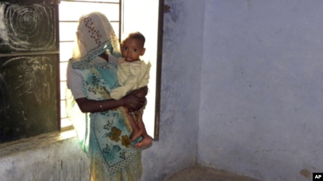 Phul Kumari, 25, stands with her child in a village community center in Baghpat district, in India's northern state of Uttar Pradesh October 18, 2011. Kumari  was trafficked to Uttar Pradesh as a bride for her husband and has been repeatedly raped by his