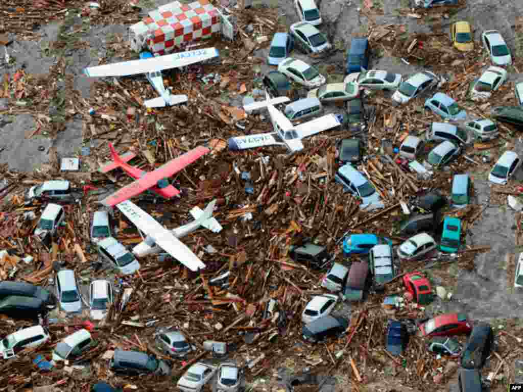 Cars and airplanes swept by a tsunami are pictured among debris at Sendai Airport, northeastern Japan March 11, 2011. A massive 8.9 magnitude quake hit northeast Japan on Friday, causing many injuries, fires and a ten-metre (33-ft) tsunami along parts of