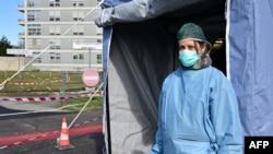意大利北方的克里莫纳医院的一名护士3月4日在医院入口检查帐篷前执守。