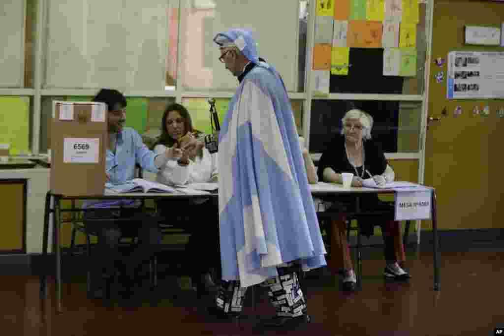 아르헨티나에서 대통령 선거를 실시한 가운데, 부에노스아이레스의 한 투표소에서 국기를 몸에 두른 유권자가 본인 확인을 하고 있다.