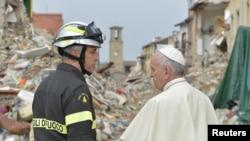 Le pape François parle avec un pompier à Amatrice, Italie, le 4 octobre 2016.