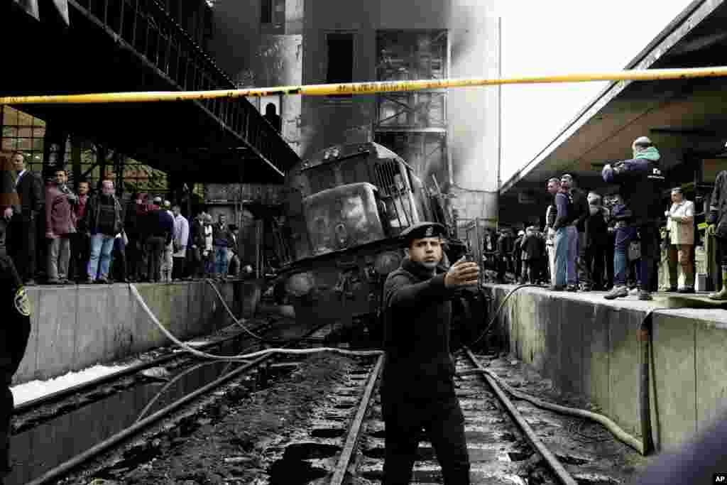 Policemen stand guard in front of a damaged train inside Ramsis train station in Cairo, Egypt. A medical official said at least 20 people have been killed and dozens injured after a railcar rammed into a barrier inside the station, which caused an explosion of the fuel tank and a huge fire.