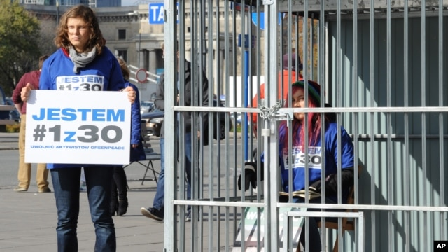 "A Greenpeace activist sits in a cage and another one holds a placard reading ""I am 1of the 30"" in a protest against the imprisonment of Greenpeace activists in Russia, in downtown Warsaw, Poland, Oct. 2, 2013."
