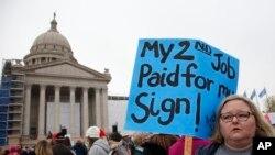 Melissa Knight, qui enseigne l'art au collège d'Ardmore, dans l'Oklahoma, tient une pancarte à l'occasion du rassemblement des enseignants au State Capitol à Oklahoma City, le lundi 2 avril 2018, pour protester contre le manque de financement des écoles.