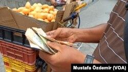 Caracas'ta bir sokak satıcısı para sayarken