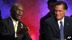 Republican presidential candidate and businessman Herman Cain speaks as former Massachusetts Governor Mitt Romney listens during a Republican presidential debate at Dartmouth College in Hanover, New Hampshire, October 11, 2011.