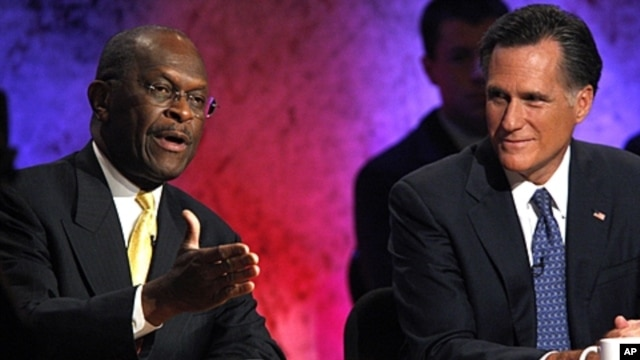 Republican presidential candidate and businessman Herman Cain (l) speaks as former Massachusetts Governor Mitt Romney listens during a Republican presidential debate at Dartmouth College in Hanover, New Hampshire, October 11, 2011.