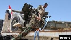 Thành viên lực lượng an ninh Iraq giúp đồng đội lên xe ở ngoại ô Fallujah, Iraq, ngày 11/6/2016.