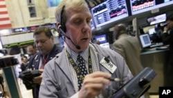 Trader Richard Cohen, right, works on the floor of the New York Stock Exchange, September 7, 2012.