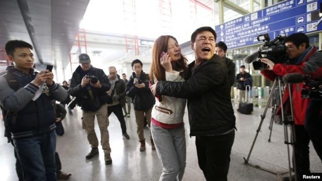Một người thân của hành khách trên chuyến bay khóc trên điện thoại tại sân bay quốc tế ở Bắc Kinh, ngày 8 tháng 3, 2014.