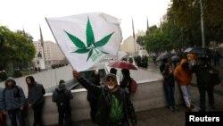 Seorang pria melambaikan bendera dalam sebuah rapat akbat menentang perdagangan narkoba untuk mendukung legalisasi budidaya marijuana pribadi untuk tujuan pengobatan dan rekreasi di Santiago, Chile tanggal 20 April 2017 (foto: REUTERS/Ivan Alvarado)