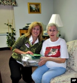 Home Instead's Kendra Kielbasa presents Kay Mamona with a Christmas gift