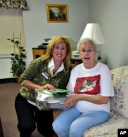 Home Instead's Kendra Kielbasa presents Kay Mamona with a Christmas gift