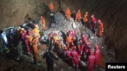 Rescuers surround the area where they found a survivor under a collapsed building at the site of a landslide that hit an industrial park on Sunday, in Shenzhen, Guangdong province, China, Dec. 23, 2015.