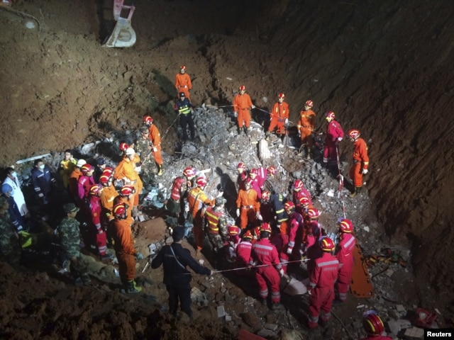 Rescuers surround the area where they found a 19-year-old survivor under a collapsed building at the site of a landslide which hit an industrial park on Sunday, in Shenzhen, Guangdong province, Dec. 23, 2015.