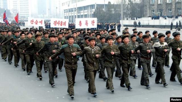North Korean students attend a contest of singing wartime songs in chorus while marching in array, at Kim Il Sung square in Pyongyang in this picture released by the North's KCNA news agency March 17, 2013.