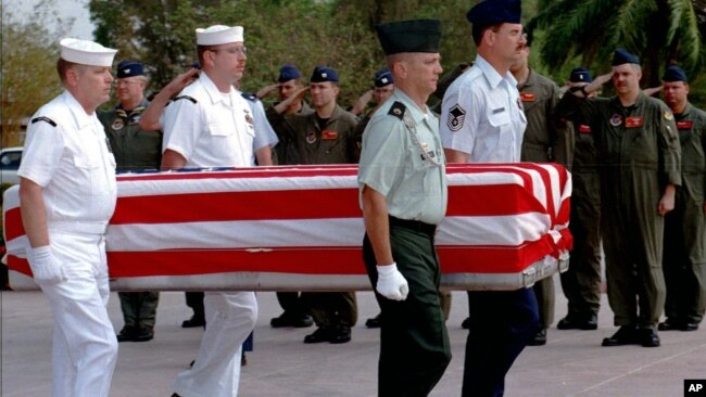 FILE PHOTO - Four U.S. servicemen carry a coffin containing the remains of U.S. servicemen from the Vietnam War era to an American military transport aircraft as U.S. pilots salute during a repatriation ceremony at the Phnom Penh airport.