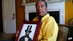 Ocea Thomas poses with a portrait of her ancestor, Samuel Burris, a free black man convicted of helping slaves escape in the 19th century. Gov. Jack Markell expects to pardon Burris, who died in 1863.
