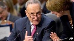 El senador Chuck Schumer consulta con una colega sobre las enmiendas a la reforma migratoria.