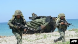 Philippine marines take position next to US Marines Amphibious Assault Vehicles (AAV) during an amphibious landing exercise at the beach of the Philippine navy training center facing the South China Sea in San Antonio town, Zambales province, north of Man