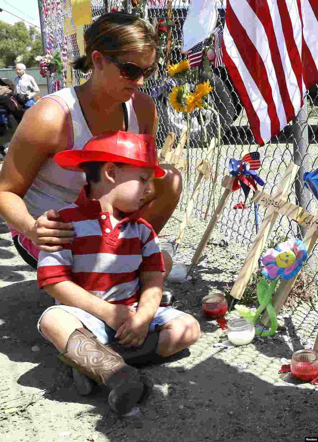 Casen Beyea, 3, wearing a toy fireman helmet looks at the cross for Andrew Ashcrast with his mother Christine at a memorial in Prescott, Arizona, July 2, 2013.