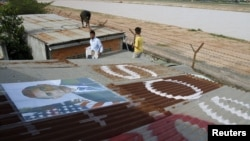 People display portraits of U.S. President Barack Obama on the roof of their houses near Phnom Penh Airport November 14, 2012. Around 182 families living around the airport have been served with eviction notices ahead of Obama's historic visit to the country.